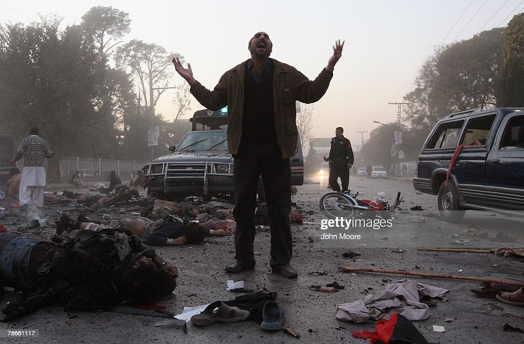 A survivor stands amidst the carnage of dead and wounded following a bomb blast attack on former Prime Minister Benazir Bhutto December 27, 2007 in Rawalpindi, Pakistan. The opposition leader has died from wounds to the neck and head after speaking at an election rally in the northern city where an estimated 15 people were left dead by the explosion, party officials have been quoted as saying.