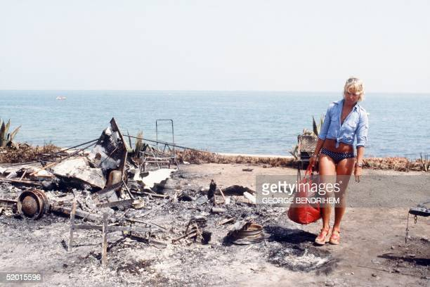 A survivor walks past a burned out camping car 12 July 1978 at Los Alfaques campsite devastated at 03 pm 11 July 1978 by a propane gas explosion...