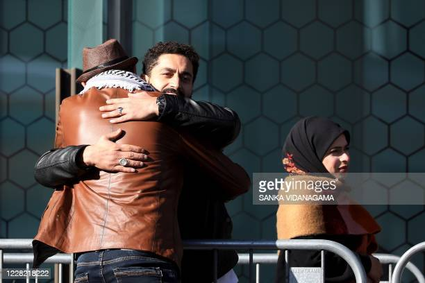 Survivors and family members of the 2019 twin mosque shootings greet each other outside the High Court building on the last day of the sentencing...