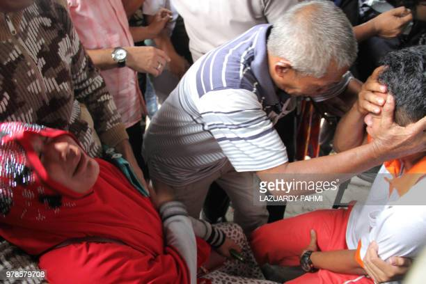 Survivors and family members react as they meet each other at the Lake Toba ferry port in the province of North Sumatra on June 19 after a boat...