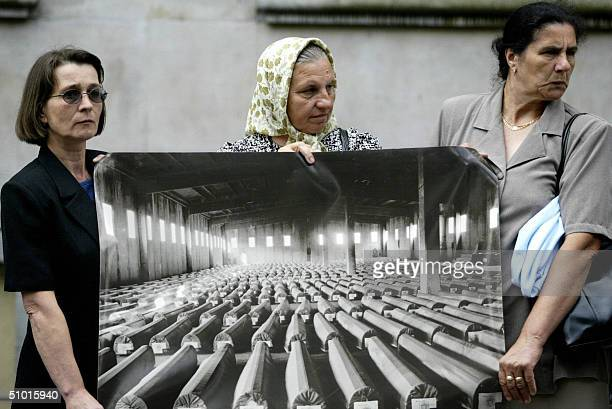 Survivors and relatives of victims of the Srebrenica massacre protest in The Hague 01 July 2004 holding a picture taken 30 March 2003 showing some...