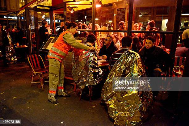 Survivors are tended to at a cafe after gunfire in the Bataclan concert hall on November 13, 2015 in Paris, France. According to reports, over 150...