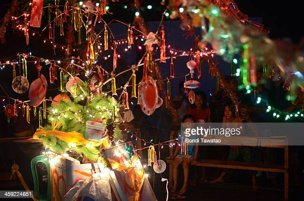 TACLOBAN LEYTE PHILIPPINES DECEMBER 24 Survivors cheer after a Christmas tree they built using storm debris is lit up on Christmas eve on December 24...
