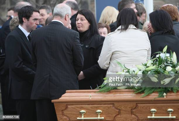 Survivors Donal Walsh and Laurance Wilson speak to Andrea near to her husband Captain Michael Evans' coffin after a funeral service at Sinclair...