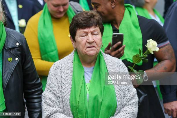 Survivors family and friends of the victims wearing symbolic green scarf in grief outside St Helen's Church during the commemoration The Grenfell...