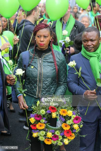 Survivors family and friends of the victims wearing symbolic green scarf and holding flowers outside St Helen's Church during the commemoration The...