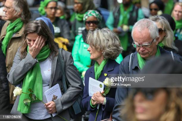 Survivors family and friends of the victims wearing symbolic green scarf take part in a silent marching from St Helen's Church to Grenfell Tower...