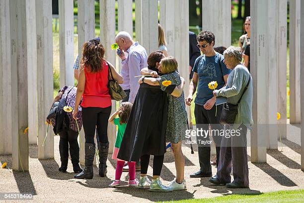 Survivors friends and relatives of the victims of the London bombings lay flowers and embrace at the 7/7 memorial on July 7 2016 in London England...