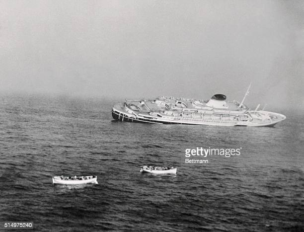 Survivors in two life boats leave the lifeless Andrea Doria as the Italian vessel slowly sinks deeper and deeper into the waters off Nantuckett