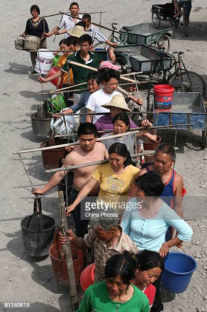 Survivors line up to fetch drinking water at the Luoshui Township on May 18, 2008 in Shifang of Sichuan Province, China. A major earthquake measuring...