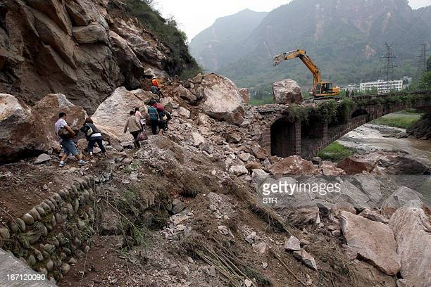 Survivors make their way along a damaged road leading to a bridge after an earthquake hit Lushan County in Ya'an City southwest China's Sichuan...