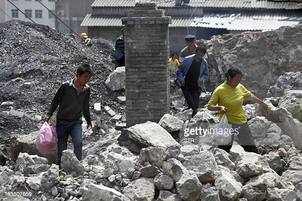 Survivors make their way through the rubble of a collapsed home in Yiliang on September 8 2012 At least 89 people were killed in earthquakes that hit...