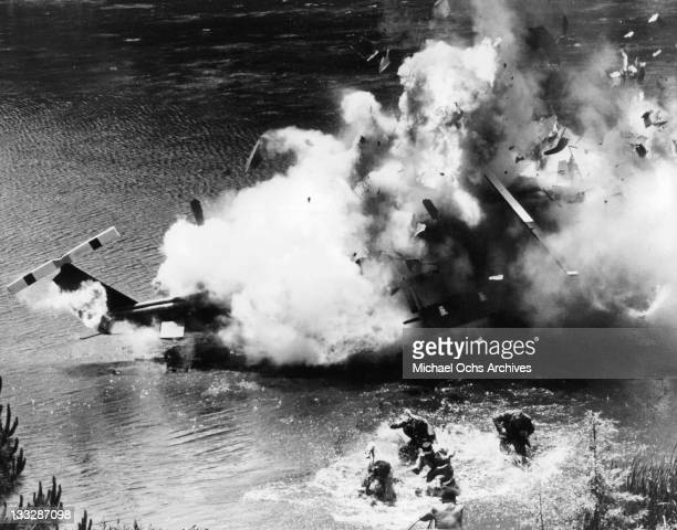 Survivors of a helicopter crash wad ashore in a scene from the film 'The Domino Principle' 1977