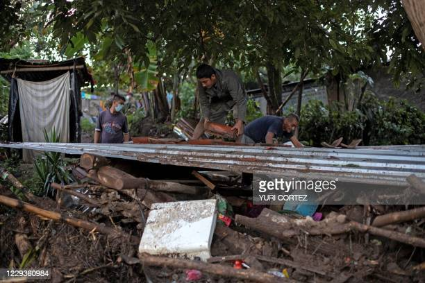 Survivors of a landslide search through the rubble of their home for belongings in Nejapa, El Salvador on October 30, 2020. - A landslide caused by...