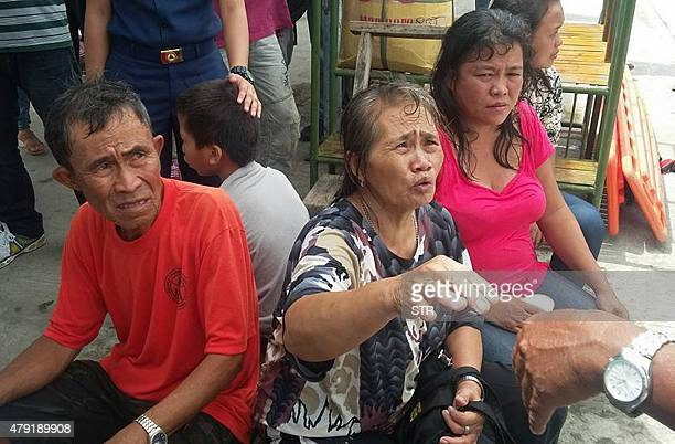 Survivors of a passenger ferry that capsized in rough waters speak to local rescue officers after arriving at the pier in Ormoc City central...