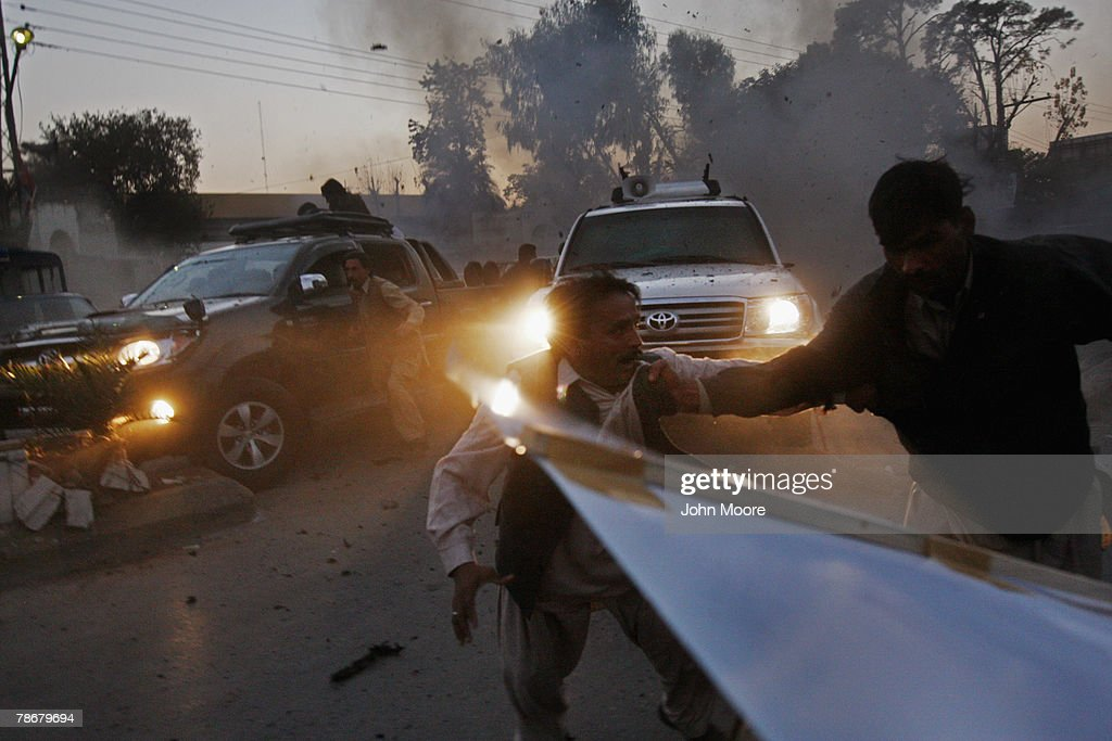 Survivors of a suicide bomb attack scramble to get out of the way as the vehicle (R), of slain former Prime Minister Benazir Bhutto speeds away from the scene of an assassination attack on Bhutto following a campaign rally December 27, 2007 in Rawalpindi, Pakistan. Bhutto was killed as she left the event, while waving to the crowd through the sun roof of her armored car. Dozens of her supporters died in a blast set off by a suicide bomber during the attack.