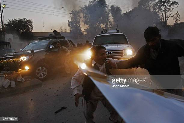Survivors of a suicide bomb attack scramble to get out of the way as the vehicle of slain former Prime Minister Benazir Bhutto speeds away from the...