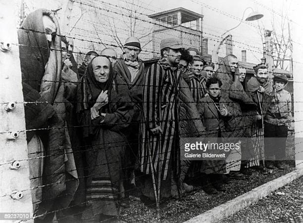 Survivors of Auschwitz behind a barbed wire fence, Poland, February 1945. Photo taken by a Russian photographer during the making of a film about the...