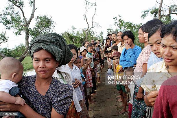 Survivors of Cyclone Nargis wait to receive rice from private donors in Dedaye in the Irrawaddy Delta some 250 miles from Yangon on June 9 2008...