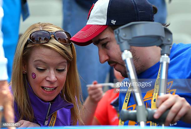 Survivors of last year's bombing, Adrianne Haslet-Davis, left, and Jeff Bauman chat in the VIP stands near the finish line of the 118th Boston...