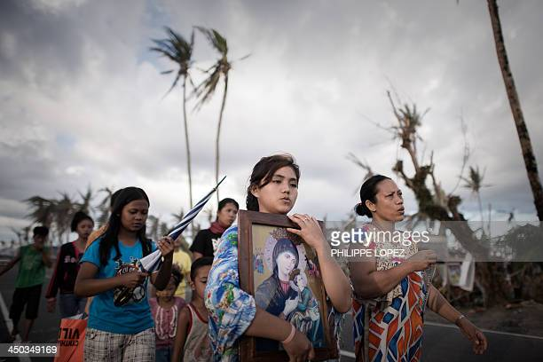 Survivors of Super Typhoon Haiyan march during a religious procession in Tolosa on the eastern Philippine island of Leyte on November 18 2013 over...