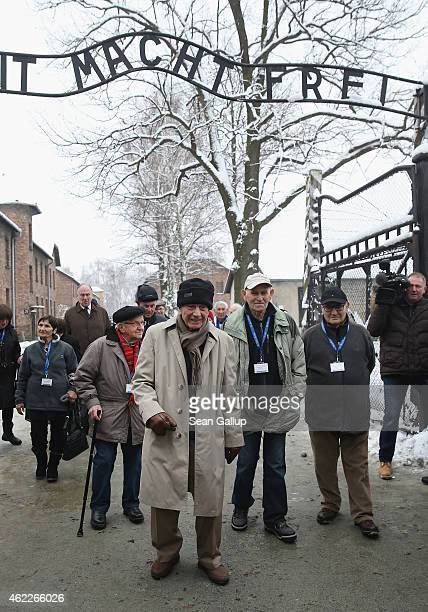 Survivors of the Auschwitz concentration camp stand at the notorious 'Arbeit Macht Frei' entrance gate while visiting the former Auschwitz I...