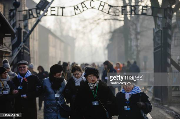 Survivors of the Auschwitz concentration camp walk by the main gate bearing the motto Arbeit Macht Frei at the former Auschwitz I site on January 27,...