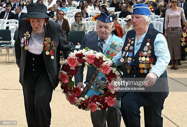 Survivors of the Holocaust lay a wreath 19 April 2004 at the Yad Vashem Holocaust Memorial in Jerusalem during Holocaust Day commemoration honoring...