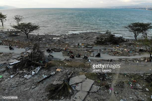 Survivors ride past debris in a devastated area in Palu Indonesia's Central Sulawesi on October 1 after an earthquake and tsunami hit the area on...