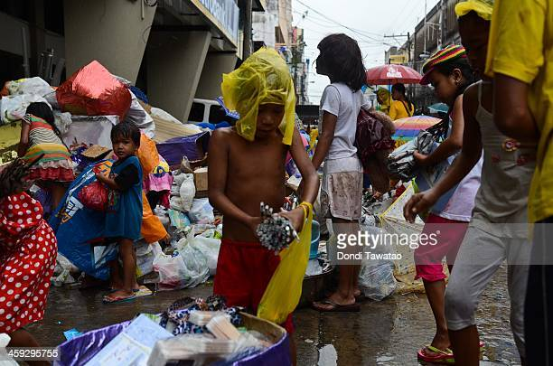TACLOBAN LEYTE PHILIPPINES DECEMBER 25 Survivors rummage through storm debris discarded by a grocery store on Christmas day on December 25 2013 in...