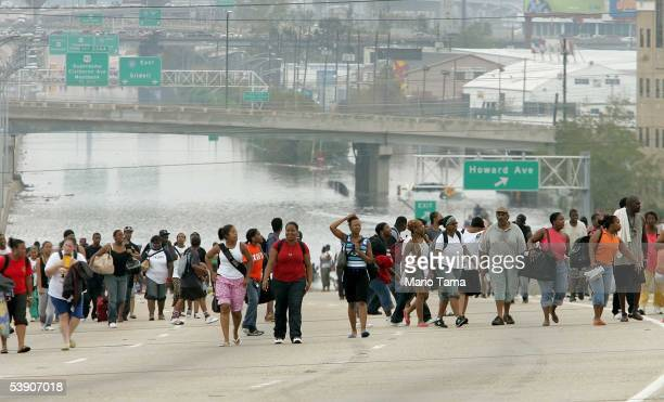 Survivors walk to high ground after being evacuated from high water to a highway September 1, 2005 in New Orleans, Louisiana. Rescue efforts continue...