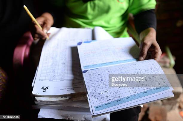 Suryana caretaker of the Mutiara Trash Bank takes notes in a ledger near her home in Makassar South Sulawesi Province Indonesia on Saturday March 12...
