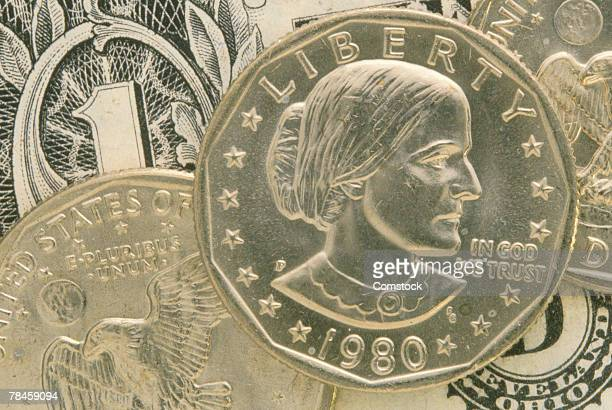 susan b anthony coin and a dollar bill - susan b anthony stock photos and pictures