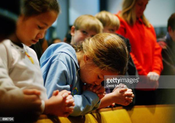 Susan bows her head in prayer as she and fellow fourth-grader Carolyne attend a prayer service to give thanks that no one has died since a car plowed...