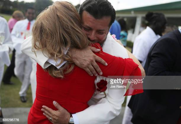 Susan Briceno hugs her husband Alonso J Briceno after participating in a group Valentine's day wedding ceremony at the National Croquet Center on...