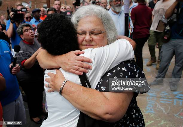 Susan Bro mother of Heather Heyer hugs a young woman near a makeshift memorial for her daughter Heather who was killed one year ago during a deadly...