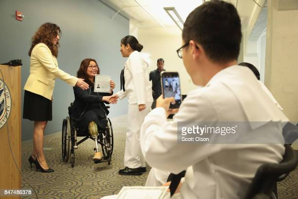 Susan Curda regional director of the US Citizenship and Immigration Services and US Senator Tammy Duckworth present Camila Tenorio who has lived in...