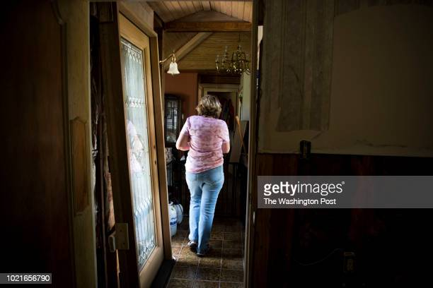 Susan Elliott walks through her home which was damaged by Hurricane Harvey in Wharton Texas on June 29 2018 The damage on the wall to the right of...
