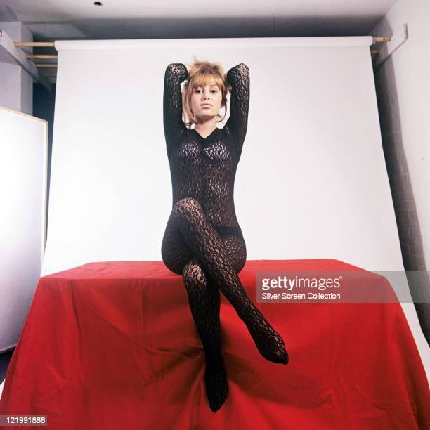 Susan George British actress wearing a black sheer fabric body stocking posing with her hands behind her head and she sits crosslegged on a red...