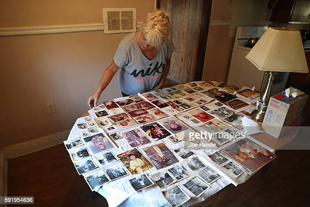 Susan Gross dries out pictures on the kitchen table in her mothers house after flood waters inundated the home with water on August 19, 2016 in St...