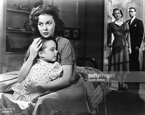 Susan Hayward holds young Gigi Perreau to her breast while Kent Smith and Lois Wheeler watch from the doorway in a scene from the film 'My Foolish...