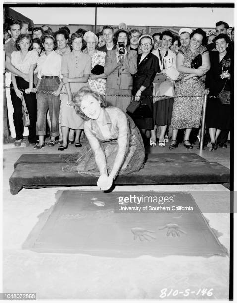 Susan Hayward putting footprints in cement at Grauman's Chinese Theater, 23 August 1951. Susan Hayward..