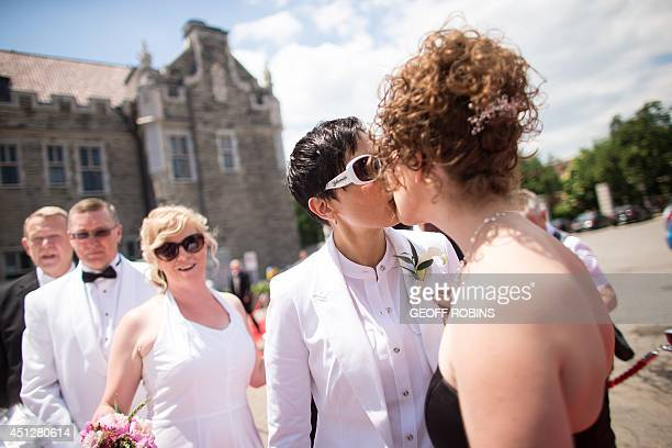 Susan Justin and her fiancee Jennifer Atkins kiss as they arrive for the Grand Pride Wedding a mass gay wedding at Casa Loma in Toronto Canada on...