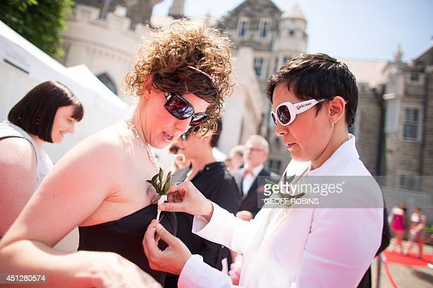 Susan Justin pins a flower on her fiancee Jennifer Atkins as they arrive for the Grand Pride Wedding a mass gay wedding at Casa Loma in Toronto...