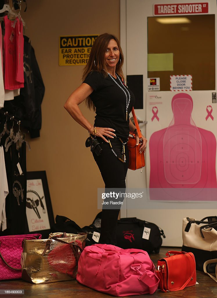 Susan Kushlin poses some of the products her company, Gun Girls, Inc., created for women that enjoy guns on October 21, 2013 in Boca Raton, Florida. Her line includes bullet jewelry, handbags, belts and custom logo apparel with some of the items priced at $35 gold-toned bullet belts, $20 dangling gun earrings, $76 pink concealed-carry handbags and $21 rhinestone-studded tank tops.