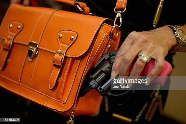 Susan Kushlin poses with a concealedcarry handbag that her company Gun Girls Inc created for women that enjoy guns on October 21 2013 in Boca Raton...