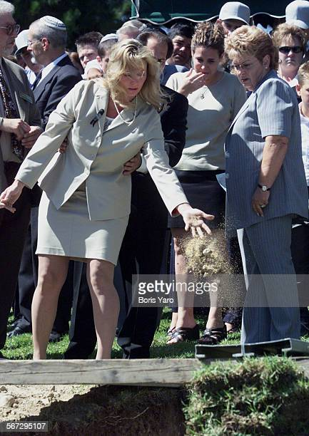 Susan Markowitz mother of slain teenager Nicholas Samuel Markowitz drops handful of dirt into his grave while his father holds onto to her ^^^/LA...