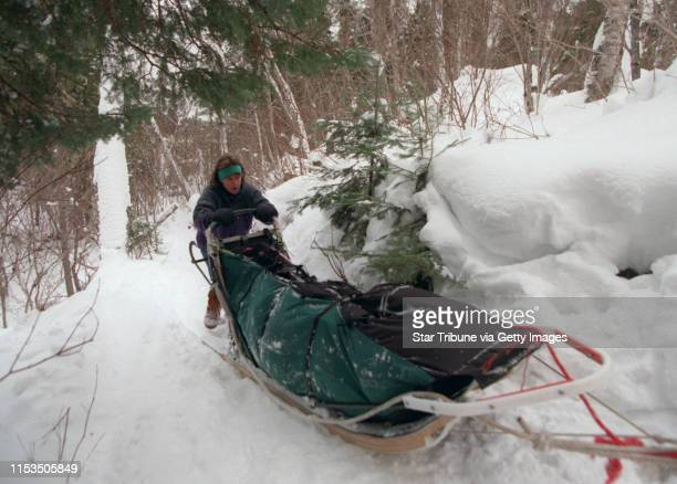 Susan McMillan of Madison helps her team of 5 dogs by pushing her sled up a hill though a portage during a recent winter camping trip in the BWCA