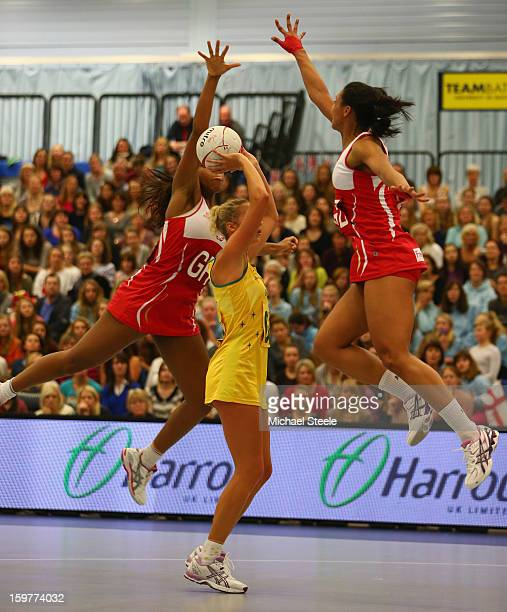 Susan Pratley of Australia manages to shoot despite the challenge of Eboni BeckfordChambers and Ama Agbeze of England during the England v Australia...