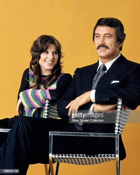 Susan Saint James US actress sitting beside Rock Hudson US actor in a studio portrait against an orange background issued as publicity for the US...